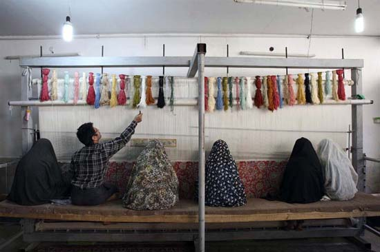 Persian Carpet Weavers in a workshop in Qom. The silk carpets of Qom are known