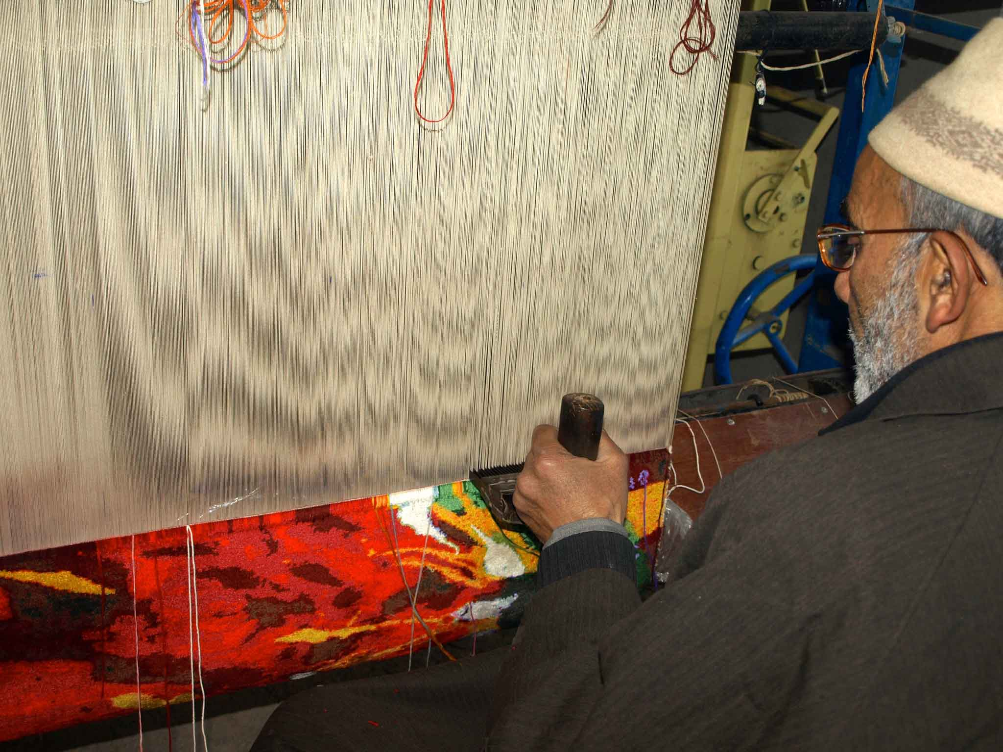 A male weaver making one of Firesun's stunning silk carpets.   Image courtesy of Firesun