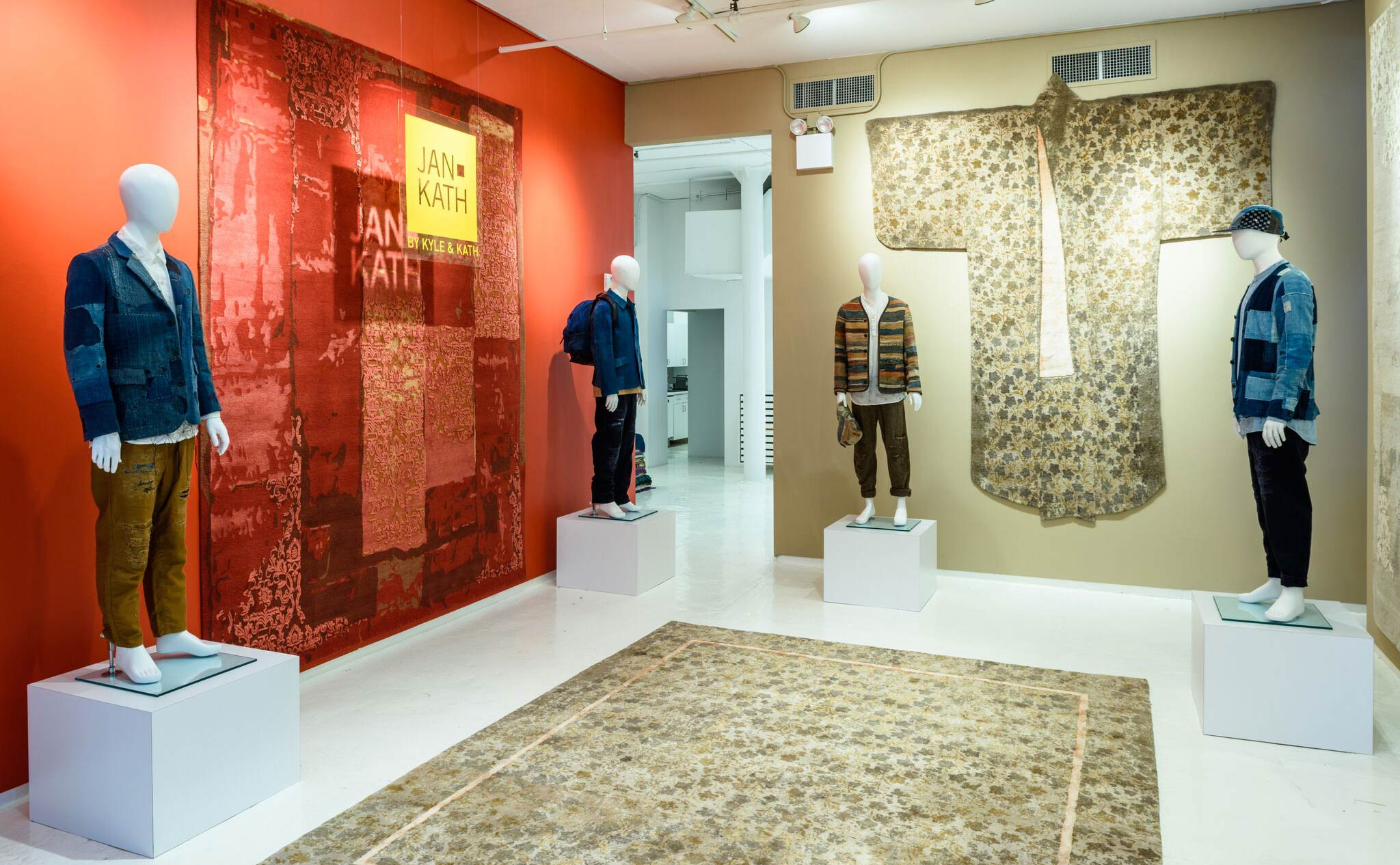 Mannequins dressed in contemporary bespoke Boro clothing from 'Kuon' ask 'What kind of exhibit are we in?' as they stand proud against an assortment of bold Jan Kath carpets including the whimsically shaped 'Dress Carpet' on the far wall. | Image courtesy of Jan Kath.