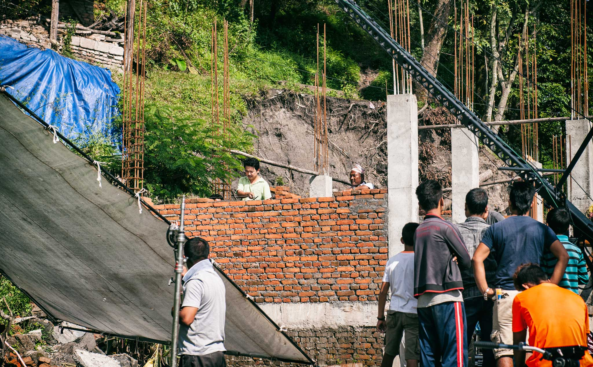 Noted Nepali stage actor Tika Bhakta Jirel is shown during filming of this house reconstruction scene in 'Nine Million Stars'. | Image courtesy of Jan Kath.