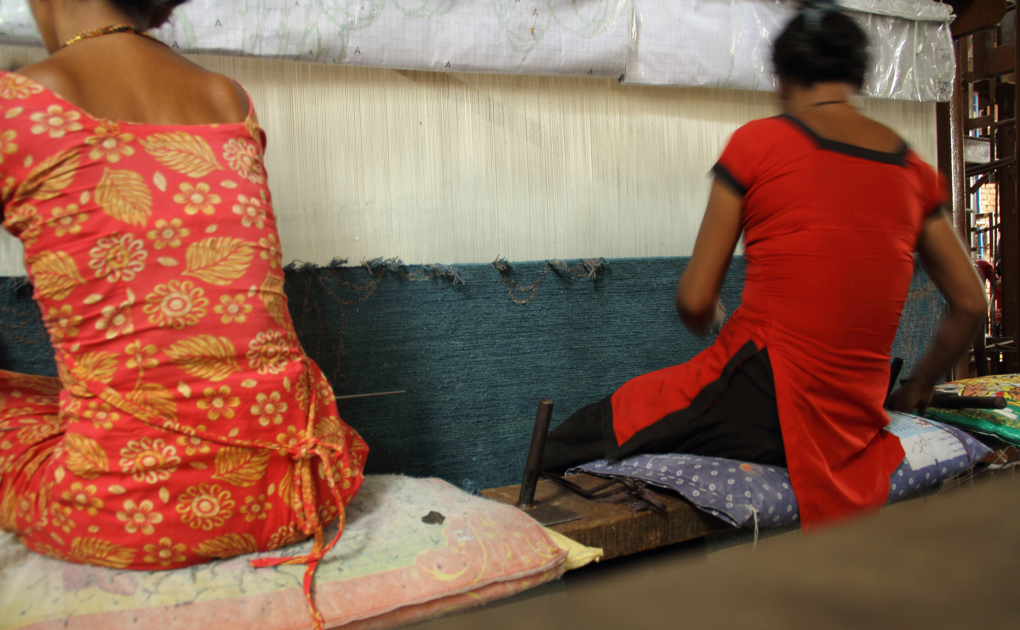'Asian Quilt' by Kooches is shown on-loom in Kathmandu being woven by two (2) Nepali women. Note the cartoon (design plate) on the loom (at the top of the image) which has the carpet design w/colour references drawn out allowing the weavers to accurately translate the design from concept to reality. | Image courtesy of Kooches.