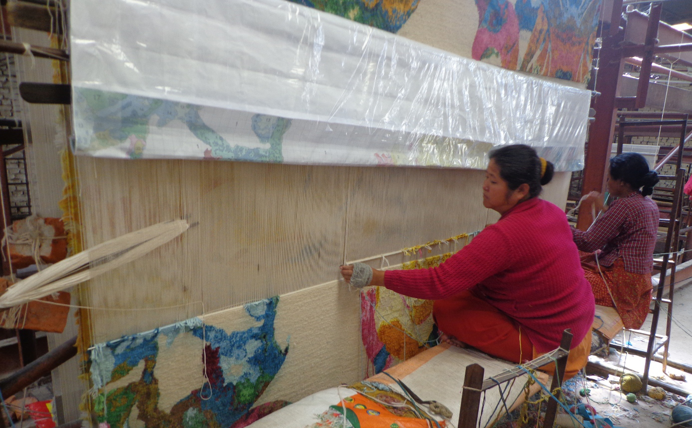 Two (2) Nepali women are shown weaving a 'Dream Vibrant' carpet from Creative Matters which appears in the first of a two part series on Nepali made carpets: The Carpets of Nepal | Part I. A carpet of this size typically has three (3) weavers working simultaneously across the width of the finished piece; the cushion for the third weaver is visible in lower left. The photographer asked that the third weaver step away from the loom for a moment to shoot the photo. | Image courtesy of Creative Matters.