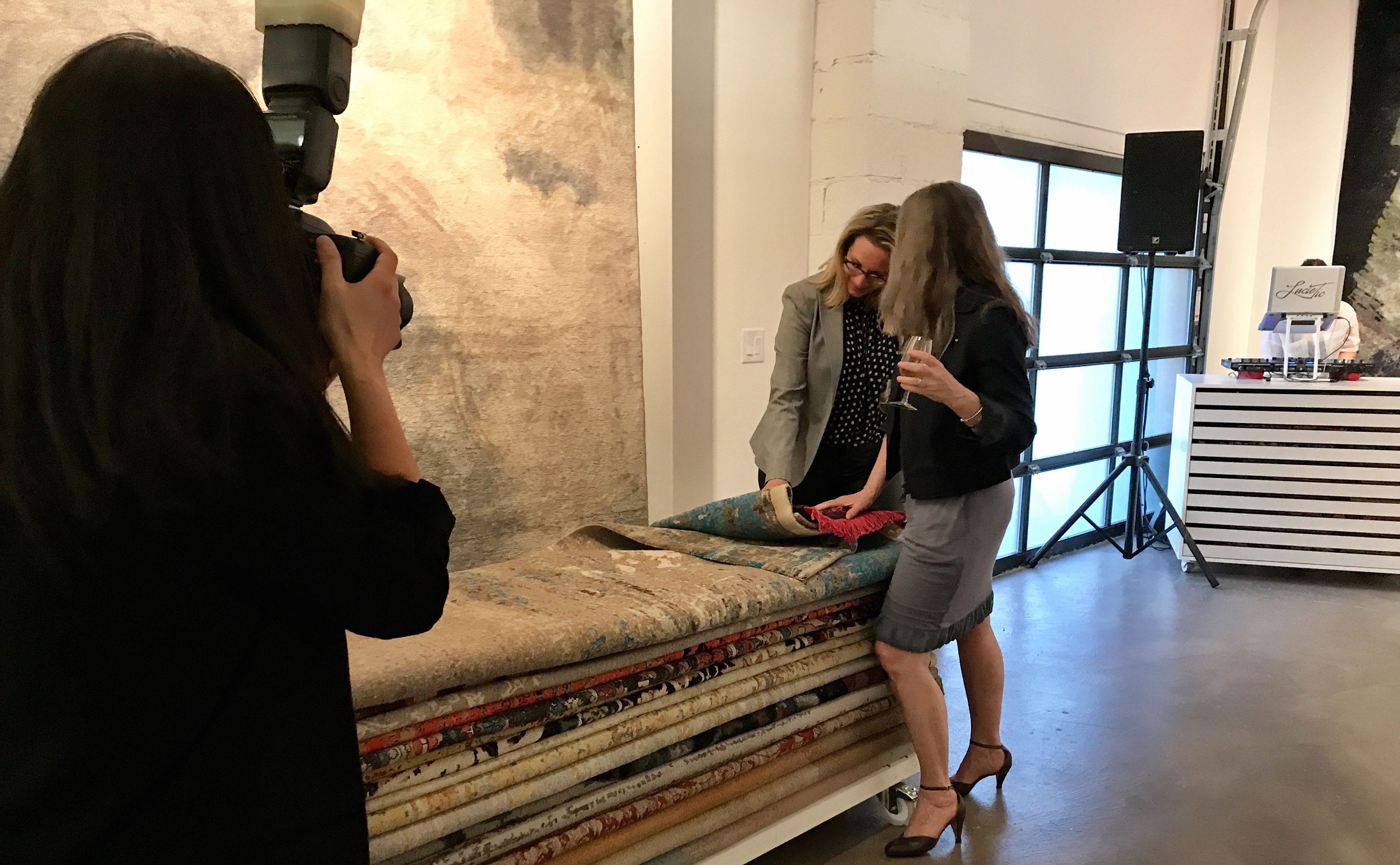 Unidentified women continue browsing at the encouragement of photographer Nancy Kim as she captures their interest during the opening of Finlay and Kath's new Jan Kath Toronto showroom on Thursday, 10 May 2018.   Image by The Ruggist.