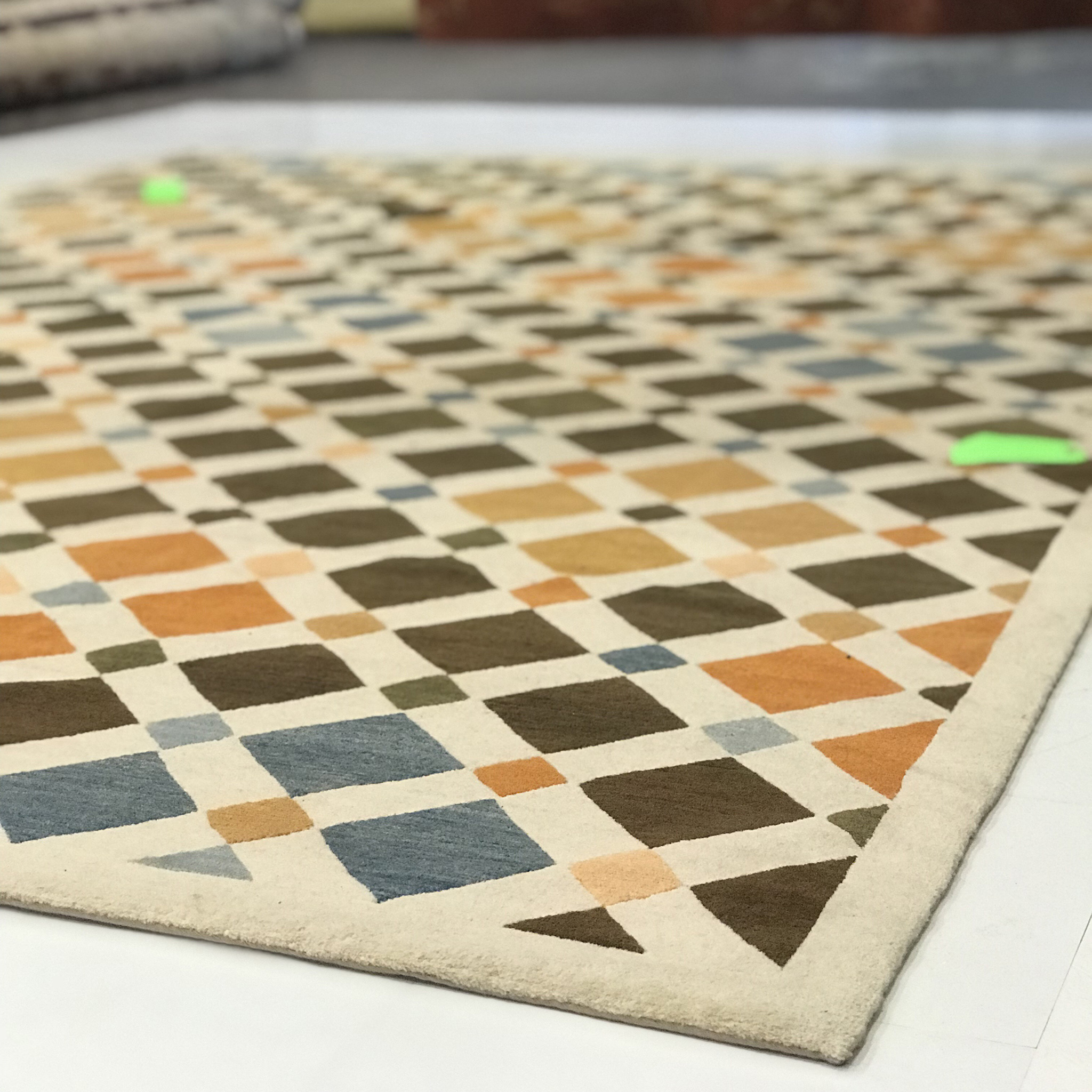 A trusted cleaner will thoroughly assess a rug or carpet prior to cleaning. Here you see 'Tile' laid flat for examination. The green tags were attached prior to shipment in order to show areas requiring extra attention.   Image courtesy of Weaver & Loom.