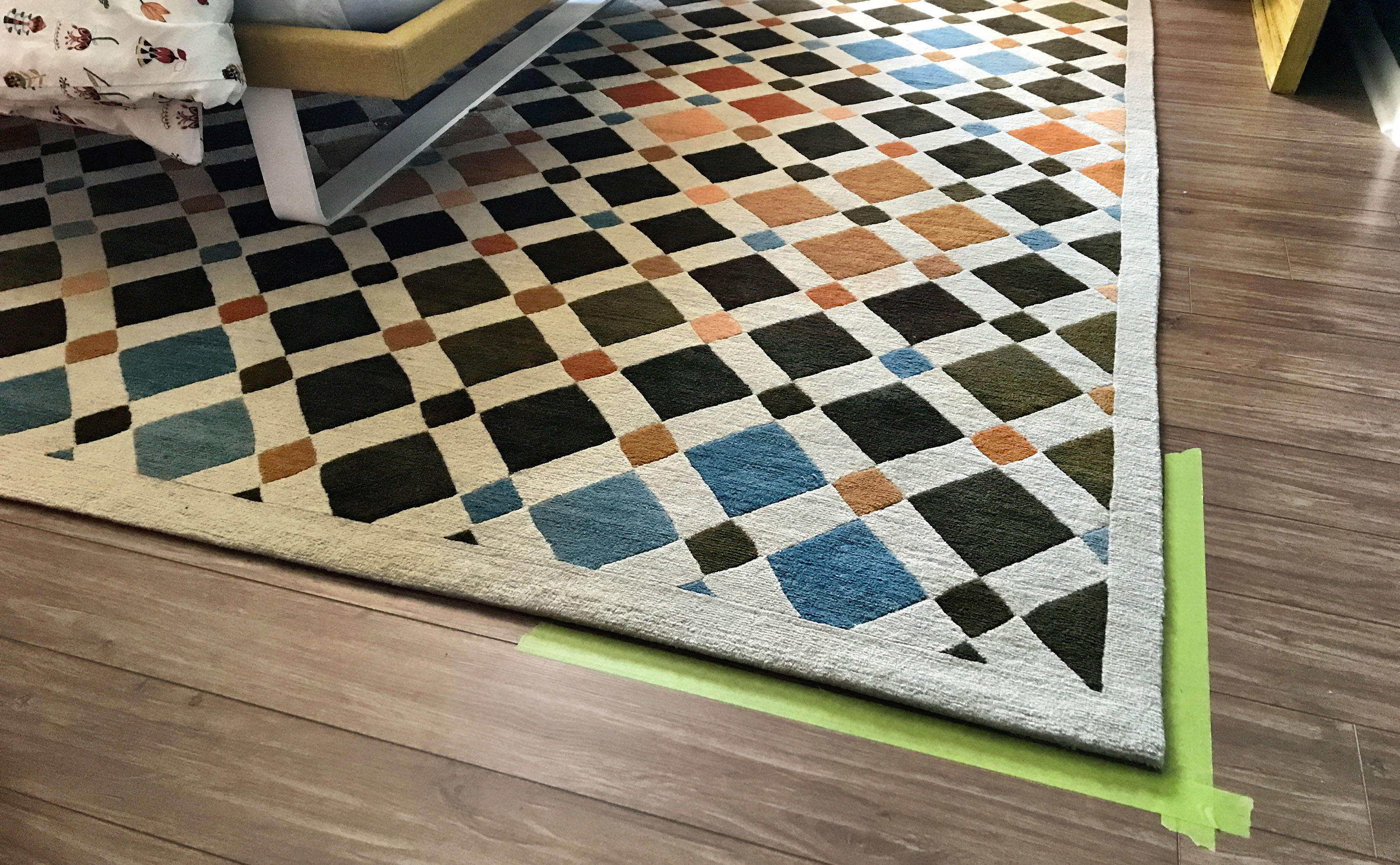 Painter's tape can be used to mark the position of a carpet prior to removal for cleaning. In tight spaces with many furnishings, marking the location of the rug makes replacing the rug after cleaning that much easier. Additionally, in situations such as this where placement is critical due to a non-clearing door sweep, the carpet must be replaced allowing for the clearance.   Image by The Ruggist.